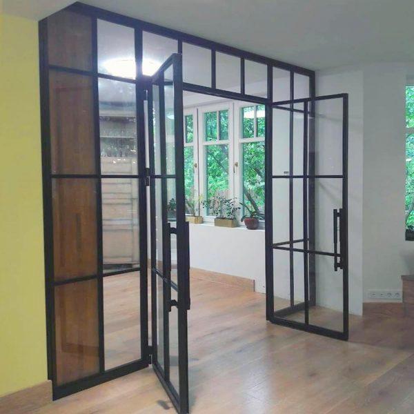 Зона кухни разделена перегородкой из стекла в стиле лофт